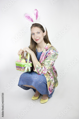 Young woman wearing rabbit ears and holding Easter basket