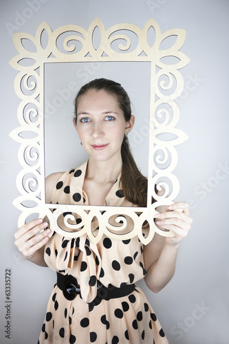 Woman wearing polka-dot dress posing with picture frame