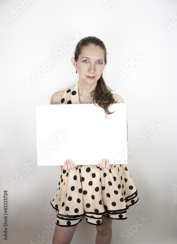 Woman wearing polka-dot dress holding blank sign