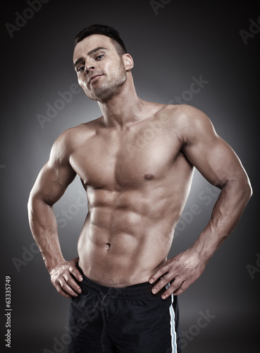 Shirtless athletic man standing akimbo