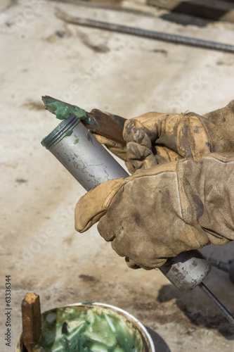 hand of a workman filling grease gun 2