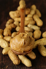 peanut butter in a wooden spoon with whole nuts