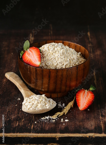 organic oat flakes with strawberries on a wooden table