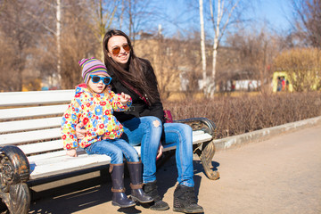 Little cute girl with her mother walking on a sunny day outdoors
