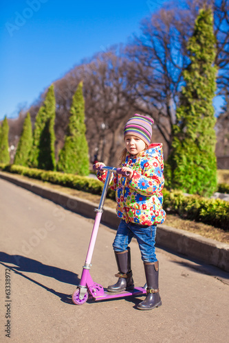 Adorable little girl have fun on the scooter in warm spring day