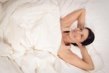 Lächelnde Frau liegt im Bett