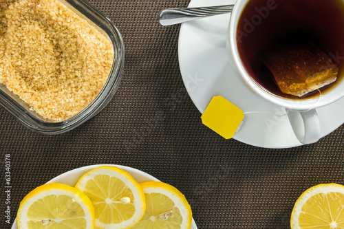 Tea cup, slices of lemon and brown sugar