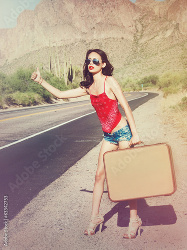 Fashion concept sexy woman hitching a ride