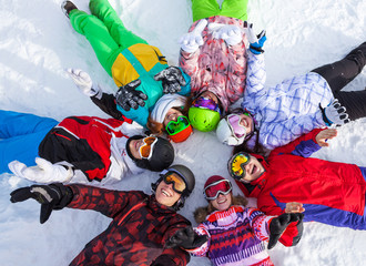 Happy snowboarders lying in circle lifting hands