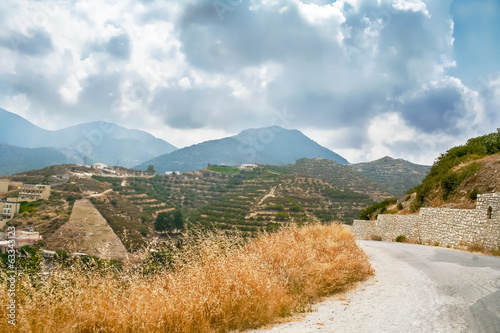 The road on the background of mountains and sky with storm cloud