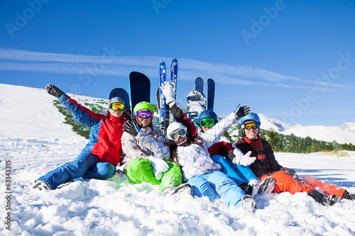 Happy friends sitting with snowboards and skis - 63343315
