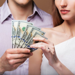 Loving couple are holding a large sum of money.