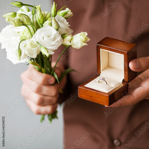 Happy man holding an engagement ring box in his hand and flowers