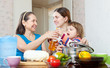 women with child cook with vegetables in kitchen