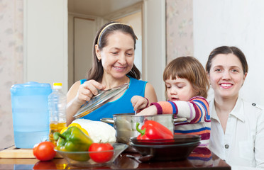 Happy family together cooking veggie lunch