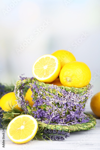 Still life with fresh lemons and lavender on light background