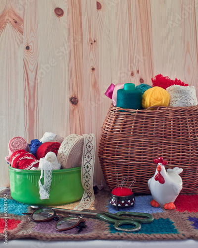 Sewing accessories in the basket. Yarn, ribbon box, glasses and
