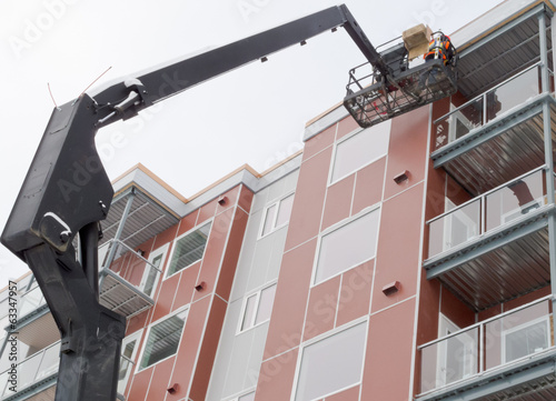 Boom lift worker work apartment highrise exterior