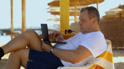 Man relaxing with a laptop at beach resort