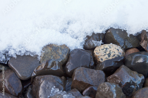 Wet stone gravel surface melting fresh snow