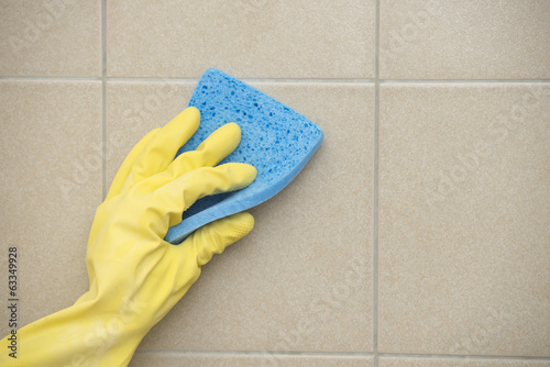 House cleaning of floor tiles with sponge