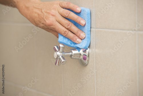 Cleaning water tap in bath with sponge