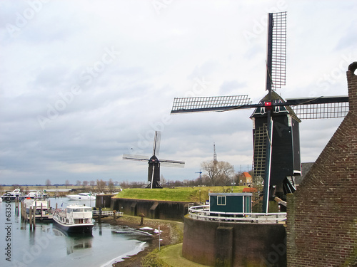 Ships and windmills in the port city Heusden. Netherlands - 63350301