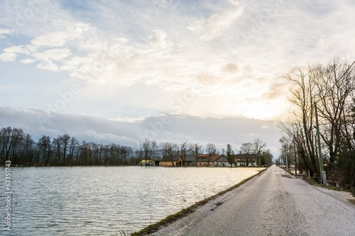 Road running along flooded field