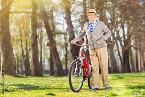 An elderly pushing his bike in the park