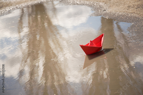 red paper boat floating in the water