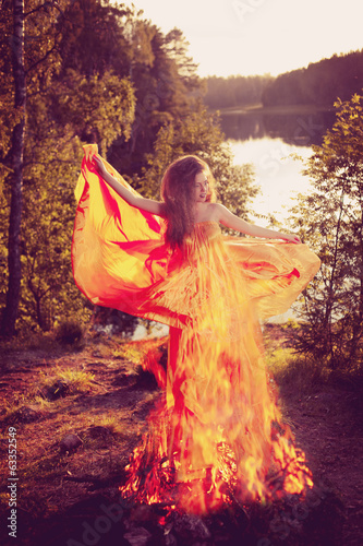 Beauty witch in the woods near the fire. Magic woman celebrating