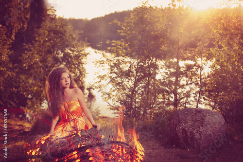 Beautiful witch in the woods near the fire. Magic woman celebrat