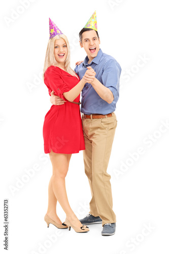 Young couple with party hats dancing