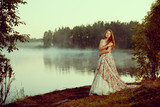 Fototapety Luxury woman in a forest in a long vintage dress near the lake.