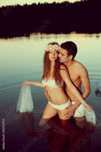 Two lovers in a lake at night. Girl and man at sunset in the lak