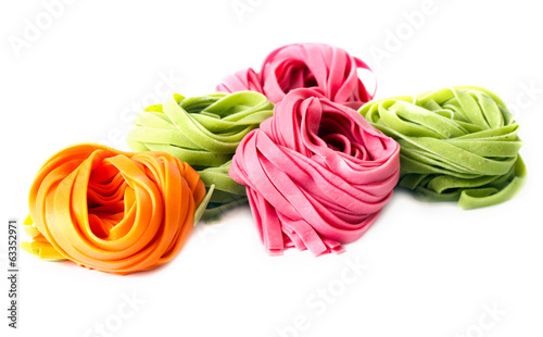Freshly made raw colorful pasta over white background