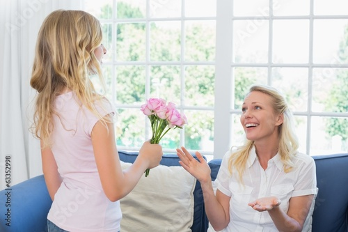 Girl giving flower bouquet to surprised mother