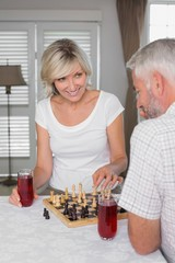 Mature couple with drinks while playing chess