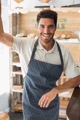 Portrait of a smiling young male barista at coffee shop