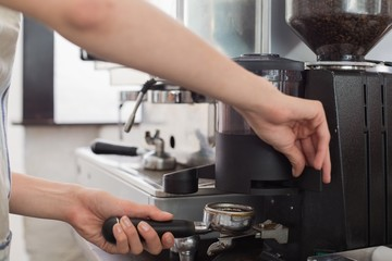 Barista prepares espresso in coffee shop