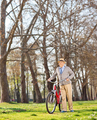 Senior gentleman pushing his bike in the park