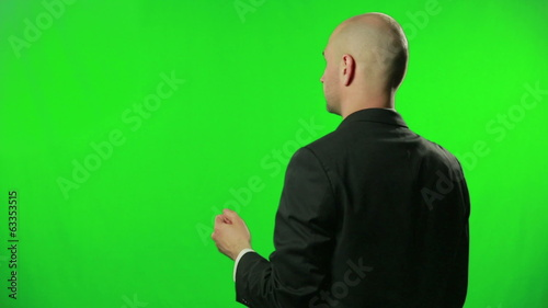 Young businessman uses touchscreen with green screen background