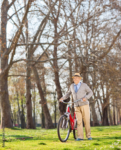 Senior gentleman pushing his bike in the park