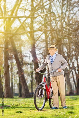 Senior man walking with his bike outdoors