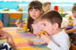 Children eating baked apple and cookie at daycare