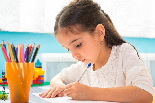 Cute hispanic girl writing at school