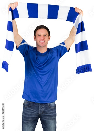 Football fan in blue holding scarf