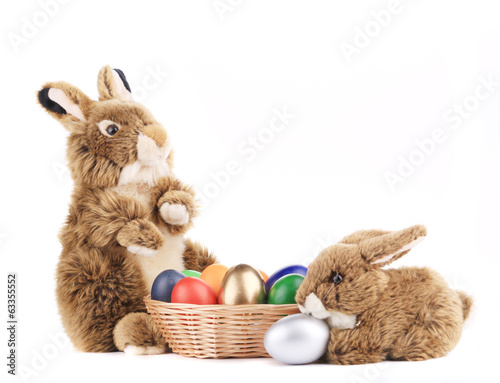 Toy rabbits with a basket of Easter eggs.