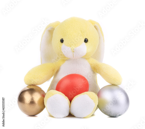 Yellow toy rabbit with easter eggs.