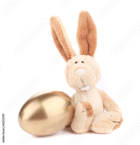 White toy rabbit with golden egg.